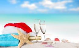 Flautas de champán con el casquillo de santa en la playa soleada Fotografía de archivo