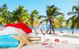 Flautas de champán con el casquillo de santa en la playa soleada Fotos de archivo