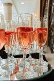 Flautas de champán festivas llenadas del vino espumoso y de las luces románticas flotantes del partido del centelleo de las fresa Imágenes de archivo libres de regalías