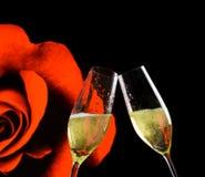 Flautas de Champagne com bolhas douradas em flores cor-de-rosa e no fundo preto Fotos de Stock Royalty Free