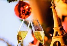 Flautas de Champagne com bolhas douradas no fundo da decoração de Eiffel do Natal Imagem de Stock