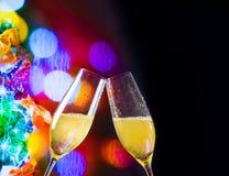 Flautas de Champagne com bolhas douradas no fundo da decoração do bokeh das luzes de Natal Fotografia de Stock Royalty Free