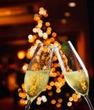 Flautas de Champagne com bolhas douradas no fundo da decoração das luzes de Natal Imagens de Stock Royalty Free