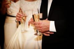 Flautas de champanhe da terra arrendada da noiva e do noivo Imagens de Stock Royalty Free