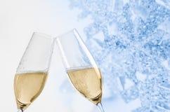 Flautas de champán con las burbujas de oro en fondo azul de la decoración de las luces de la Navidad Foto de archivo