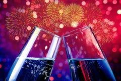 Flautas de champán con las burbujas de oro en fondo ligero rojo y púrpura de la chispa del bokeh y de los fuegos artificiales Foto de archivo