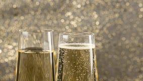 Flautas de relleno del champán con las burbujas de oro contra el fondo del bokeh del oro, concepto de Feliz Año Nuevo del día de  almacen de metraje de vídeo