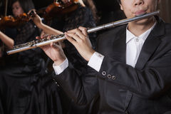 Flautist holding and playing the flute during a performance, close-up Royalty Free Stock Photography