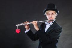 Flautista de sexo masculino con la flauta y el corazón Melodía del amor Imagen de archivo libre de regalías