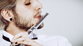Flautista de sexo masculino que juega su primer de la flauta Foto de archivo