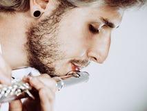 Flautista de sexo masculino que juega su primer de la flauta Imagenes de archivo