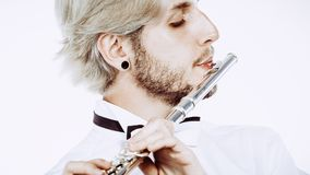Flautista de sexo masculino que toca su flauta Foto de archivo libre de regalías