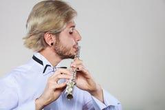 Flautista de sexo masculino que toca su flauta Imagenes de archivo