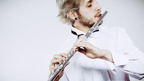 Flautista de sexo masculino que toca su flauta Fotografía de archivo libre de regalías