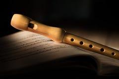 Flauto di legno con il punteggio musicale fotografia stock libera da diritti