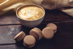 Flavored coffee cappuccino with macarons and cinnamon. The perfect Breakfast Royalty Free Stock Photo