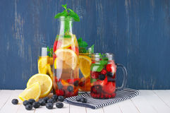 Flavored fruit infused water. Various fresh vitamin flavored fruit infused water in bottle and jar with fruits and napkin on white wooden table against blue stock images
