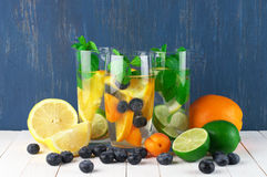 Flavored fruit infused water. Various fresh vitamin flavored fruit infused water in glasses with fruits on white wooden table against blue colored wall stock photos