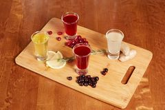 Flavored fruit liqueurs on wooden board. Citrus, berries, ginger stock image