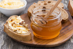 Flavored honey, bread with butter and grape on wooden board Royalty Free Stock Images