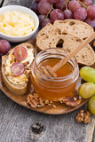 Flavored honey, bread with butter and grape on wooden board Royalty Free Stock Photo