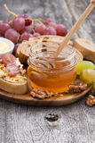 Flavored honey, bread and butter and grapes Stock Photos