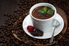 flavored hot chocolate in a cup on a background of coffee beans Royalty Free Stock Images