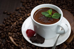 Flavored hot chocolate in a cup on a background of coffee beans Stock Image