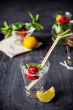 Flavored water with fresh strawberries and mint in glass on a black wooden table with bright details.Selective focus, close up Stock Photography