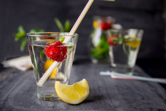 Flavored water with fresh strawberries and mint in glass on a black wooden table with bright details.Selective focus, close up.  Stock Photos