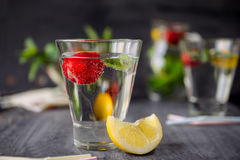 Flavored water with fresh strawberries and mint in glass on a black wooden table with bright details.Selective focus, close up.  Stock Photo
