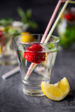 Flavored water with fresh strawberries and mint in glass on a black wooden table with bright details.Selective focus, close up.  Royalty Free Stock Photography