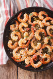 Flavorful food: shrimp in garlic sauce with parmesan cheese and. Herbs closeup on the table. vertical view from above Stock Images