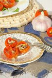Flavorful healthy starter. Oven baked cherry tomatoes with oregano and fresh chopped garlic on an old porcelain plate Royalty Free Stock Image
