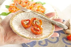 Flavorful healthy starter. Oven baked cherry tomatoes with oregano and fresh chopped garlic on an old porcelain plate kept by a woman. Served with Italian Stock Images