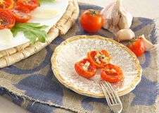Flavorful healthy starter. Oven baked cherry tomatoes with oregano and fresh chopped garlic on an old porcelain plate. Served with Italian parmesan cheese and Stock Images