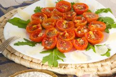 Flavorful healthy starter. Oven baked cherry tomatoes with oregano and fresh chopped garlic on a white plate. Served with Italian parmesan cheese, olive oil Stock Photo