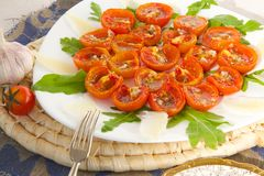 Flavorful healthy starter. Oven baked cherry tomatoes with oregano and fresh chopped garlic on a white plate. Served with Italian parmesan cheese and rucola Royalty Free Stock Image