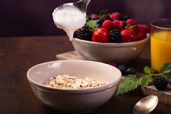 Flavoring oatmeal with white yoghurt and some berries. Spoon of yoghurt. Flavoring oatmeal with white yoghurt and some berries. Cup of fresh orange juice Stock Photography