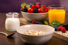 Flavoring oatmeal with white yoghurt and some berries. Spoon and yoghurt. Flavoring oatmeal with white yoghurt and some berries. Cup of fresh orange juice Stock Photography