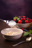 Flavoring oatmeal with white yoghurt and some berries. Spoon of yoghurt. Flavoring oatmeal with white yoghurt and some berries. Cup of fresh orange juice stock photos