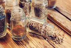 Flavorings in the bottles. Containing coriander seeds and carry on the wooden kitchen table Royalty Free Stock Photo