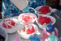 Flavouring a sweetened condensed milk snow cone shaved ice. In a white cup stock photography