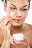 Flawless-skinned woman with moisturizing face cream Stock Images