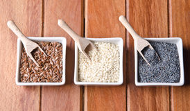 Flax, poppy and sesame seeds. In little bowls on a wood table Royalty Free Stock Images