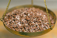 Flax-seed on a balance Stock Photography