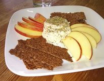 Flax Seed Crackers, Apples and Nut Cheese. An appetizer with flaxseed crackers, cut apples and a creamy nut cheese spread with herbs on a white plate Royalty Free Stock Photography