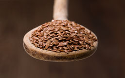 Flax Seed. Doctor recommended healthy brown flax seeds on a wooden spoon royalty free stock photo