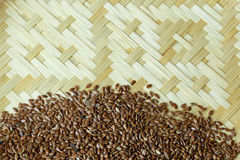 Flax seed placed on flat woven basket Royalty Free Stock Photos