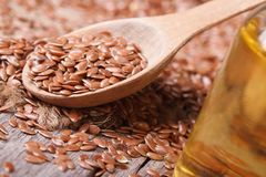 Flax seed in a spoon and oil. horizontal Stock Images